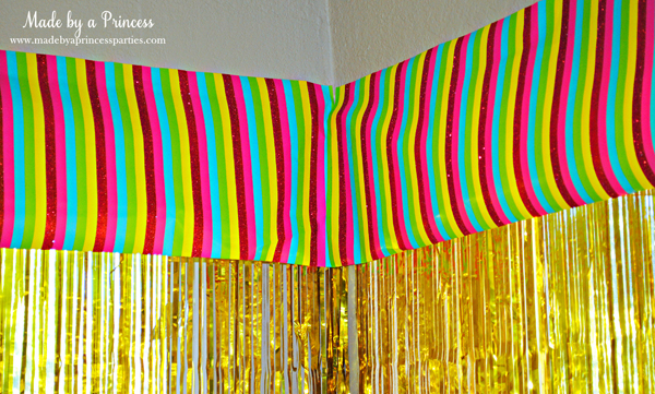 Kids St Patricks Day Party Ideas use rainbow wrapping as a window valance