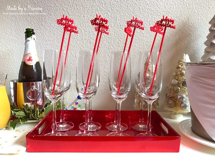 budget-friendly-holiday-mimosa-bar-party-merry-christmas-drink-stirrers-in-glasses-on-tray