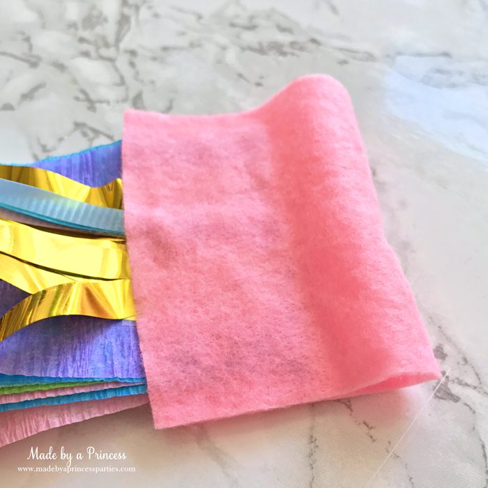 unicorn tail party idea tutorial fold piece of felt over streamers glue and trim